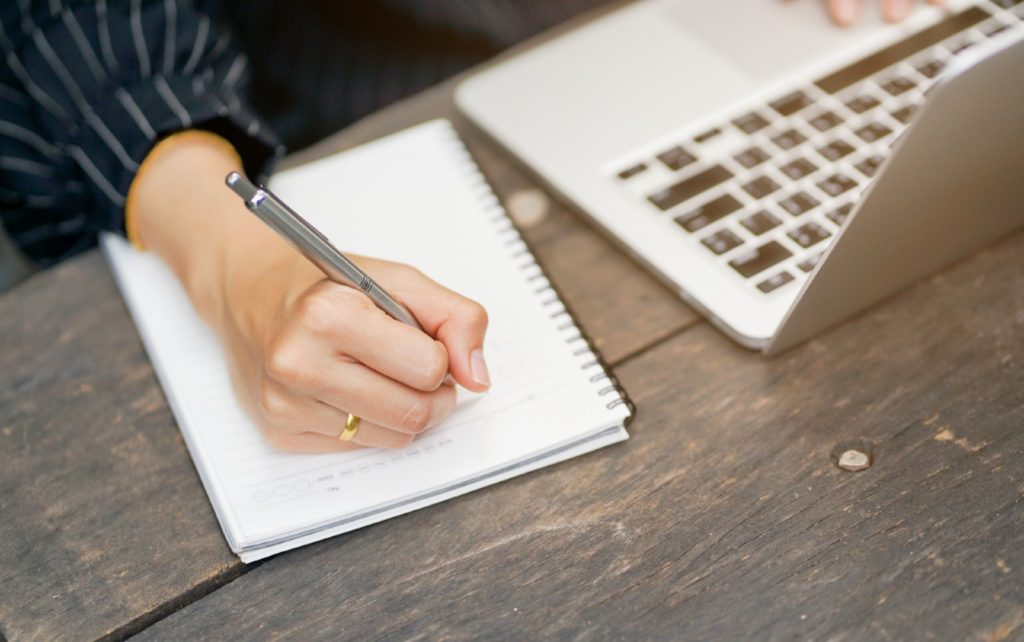 Woman writes scripted outline in notebook