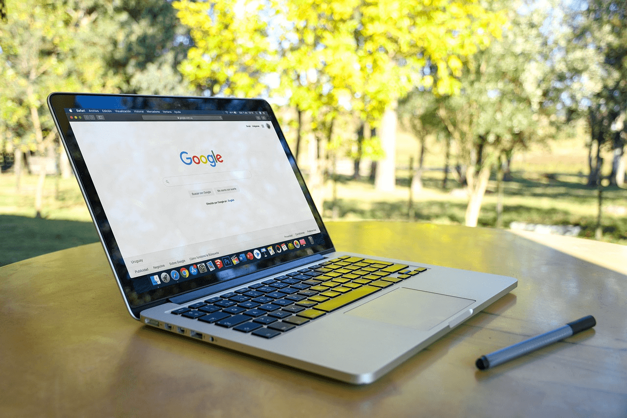 An Apple laptop placed in a local park displays the Google search engine