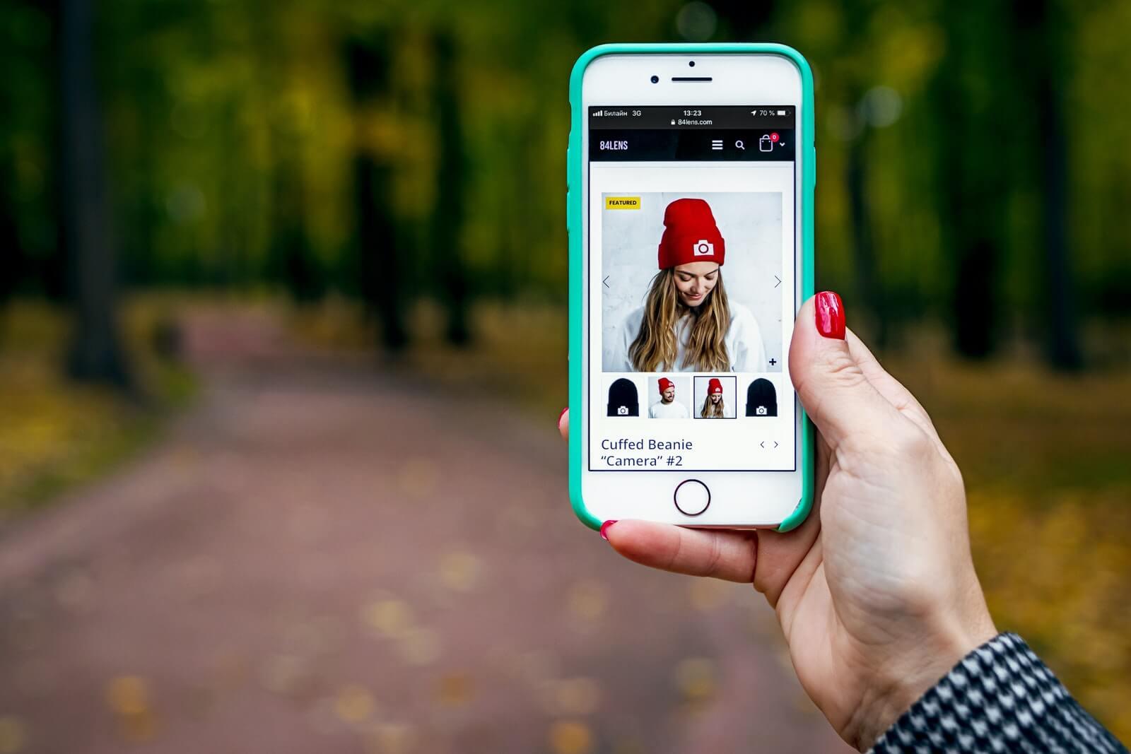 woman scrolls through digital ad on her iphone